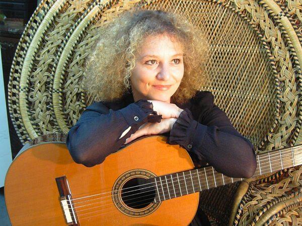 Valérie Duchâteau assise avec sa guitare